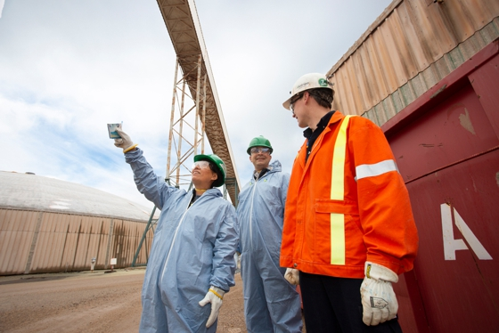 Dr. Stephanie Young, Alex Munoz, senior process engineer at Stantec Consulting Ltd., and Mark Buchinski, chief metallurgical engineer at Nutrien, at Lanigan Potash looking up at the conveyor gallery where raw ore enters the mill.